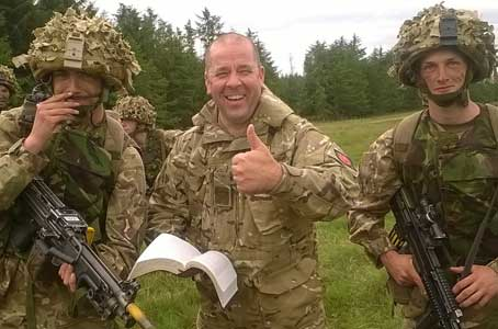 Scripture reader with troops, holding bible