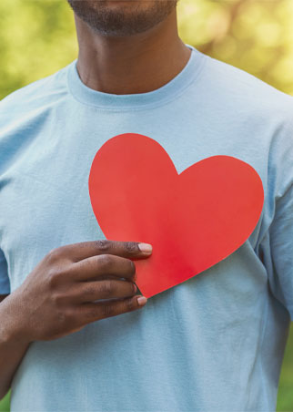 Man holding red paper heart on his chest